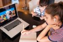 Teenage girl studying with video online lesson at home   family in isolation Homeschooling and distance learning
