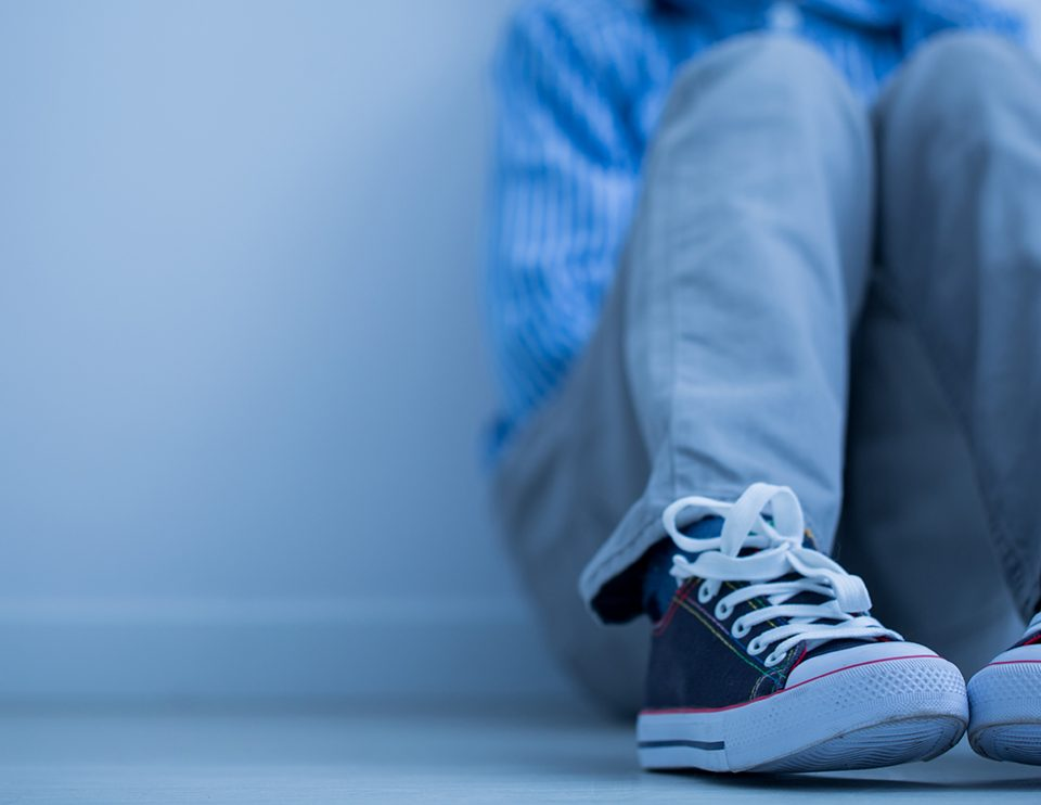 Sad boy in sneakers with asperger's syndrome sits alone in his room